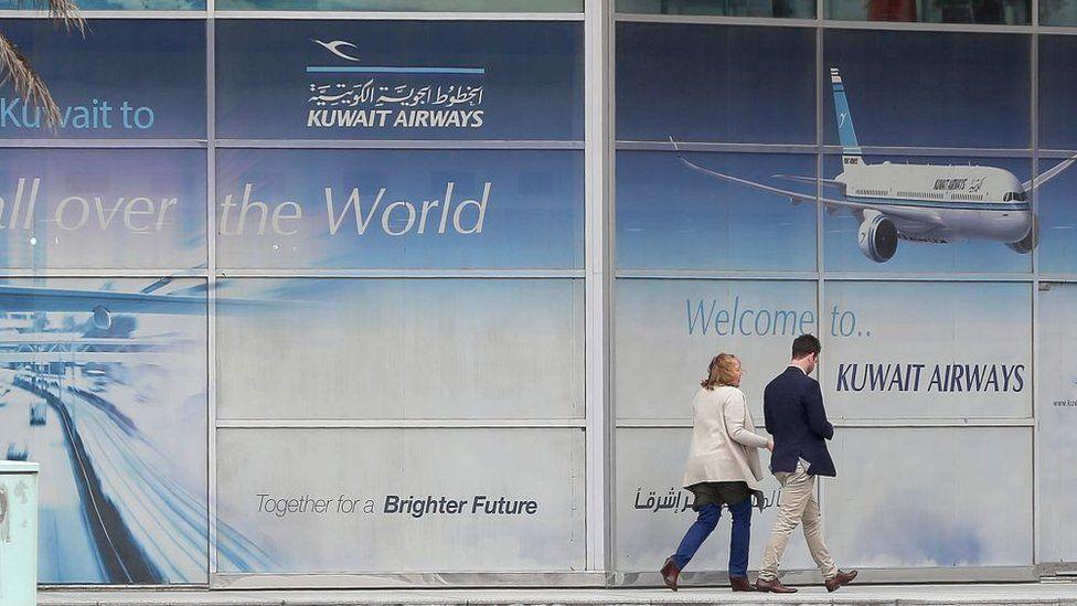 Customers walk past Kuwait Airways board in Kuwait