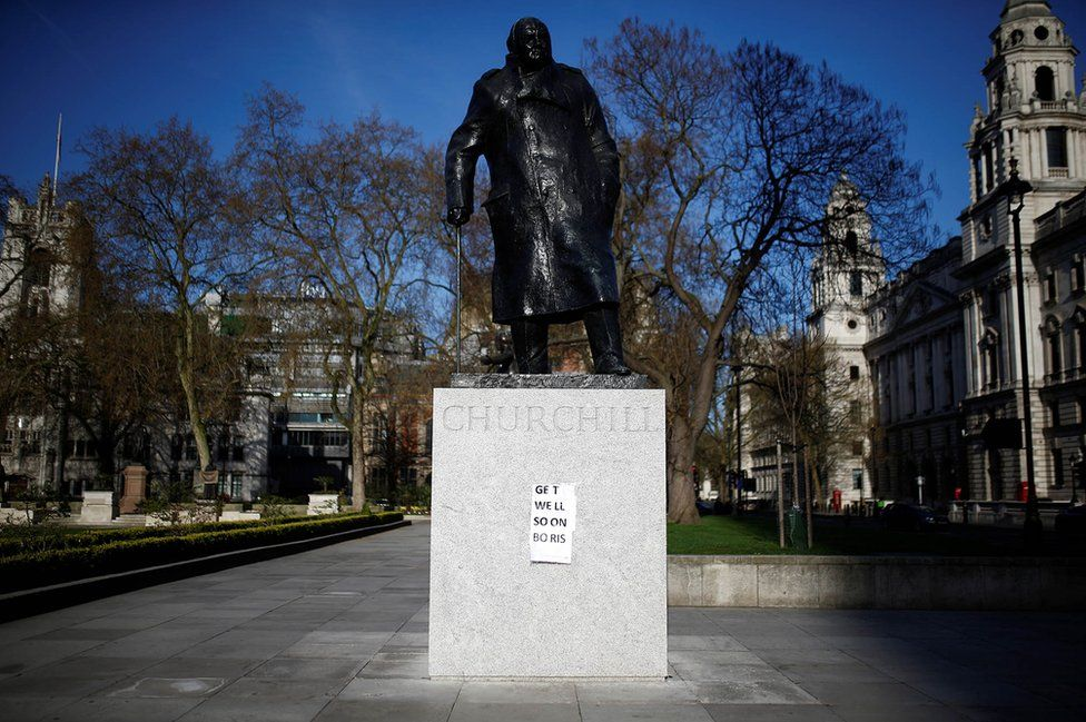 """A """"get well soon"""" message is seen attached to a statue of Sir Winston Churchill"""