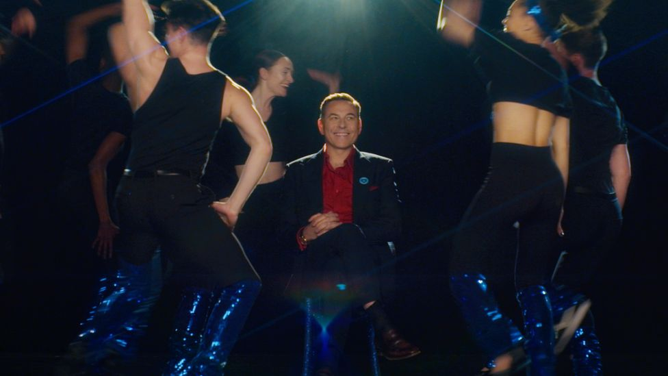 David Walliams sits among dancers in a still from the film to promte the Covid jab