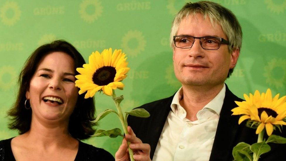 Co-leader of the Green party Annalena Baerbock and German Greens party top candidate Sven Giegold celebrate