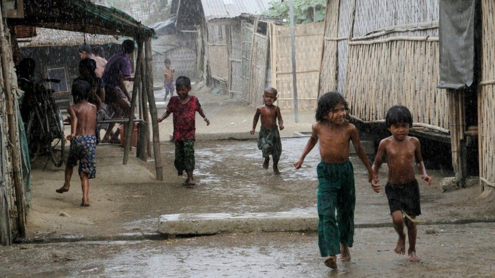 Rohingya children play during rain at an Internally Displaced Persons (IDPs) camp near Sittwe of Rakhine State, western Myanmar, 22 March 2016