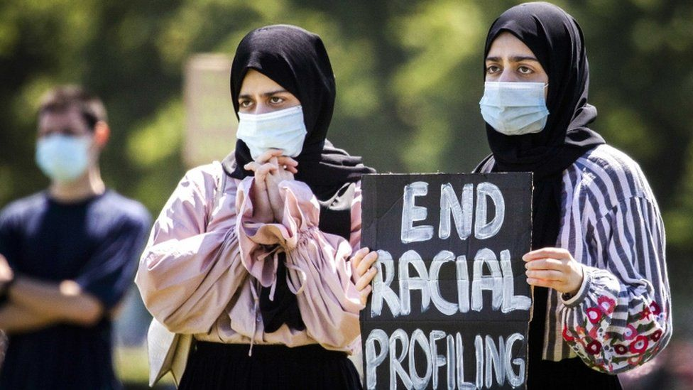 """Veiled women hold a placard as supporters and members of the Dutch action group """"Kick Out Zwarte Piet"""" (KOZP) from The Hague stage their second demonstration this month at the Malieveld in The Hague"""