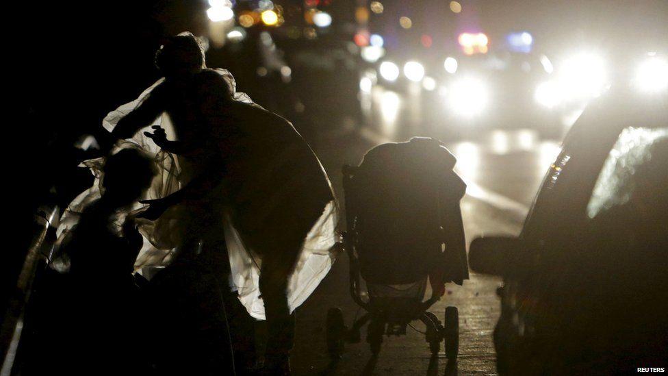 A migrants adjusts a plastic sheet in the rain