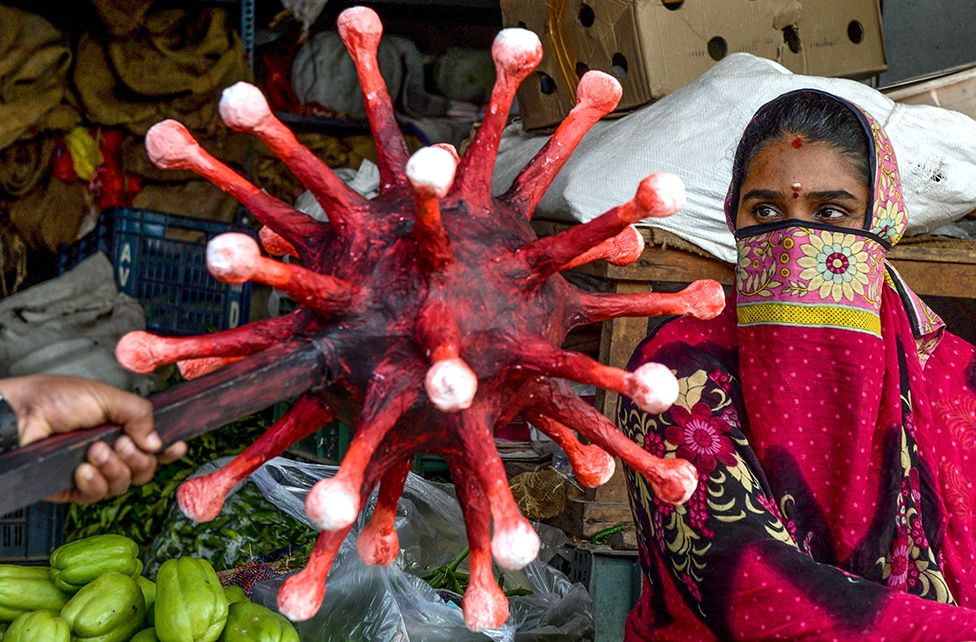A policeman gestures towards a woman with coronavirus-themed mace