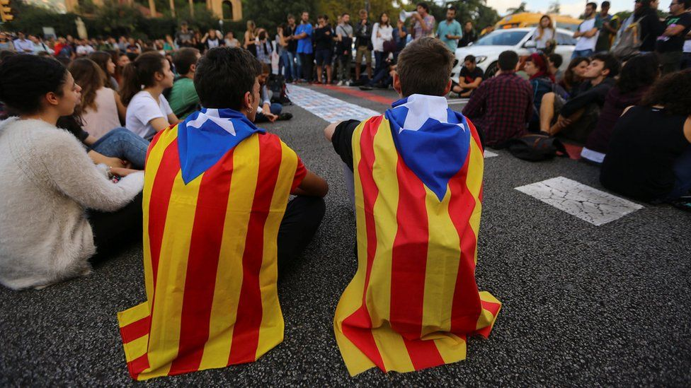 Students wear Catalan separatist flags as they block a street during a gathering to protest against the imprisonment of leaders of two of the largest Catalan separatist organizations, in Barcelona, Spain, October 17, 2017