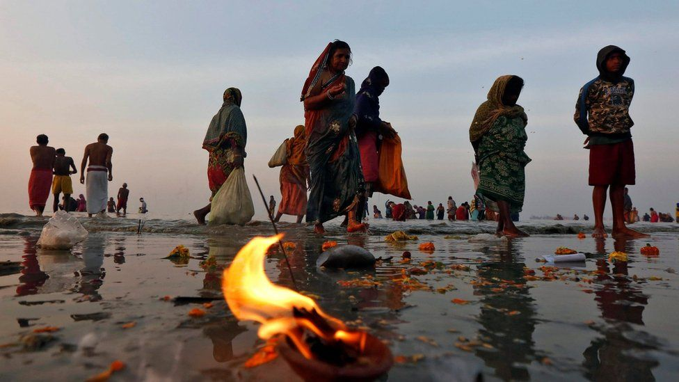 "Hindu pilgrims walk after taking a dip at the confluence of the river Ganges and the Bay of Bengal a day after ""Makar Sankranti"" festival at Sagar Island, south of Kolkata, India, on 15 January 2017"