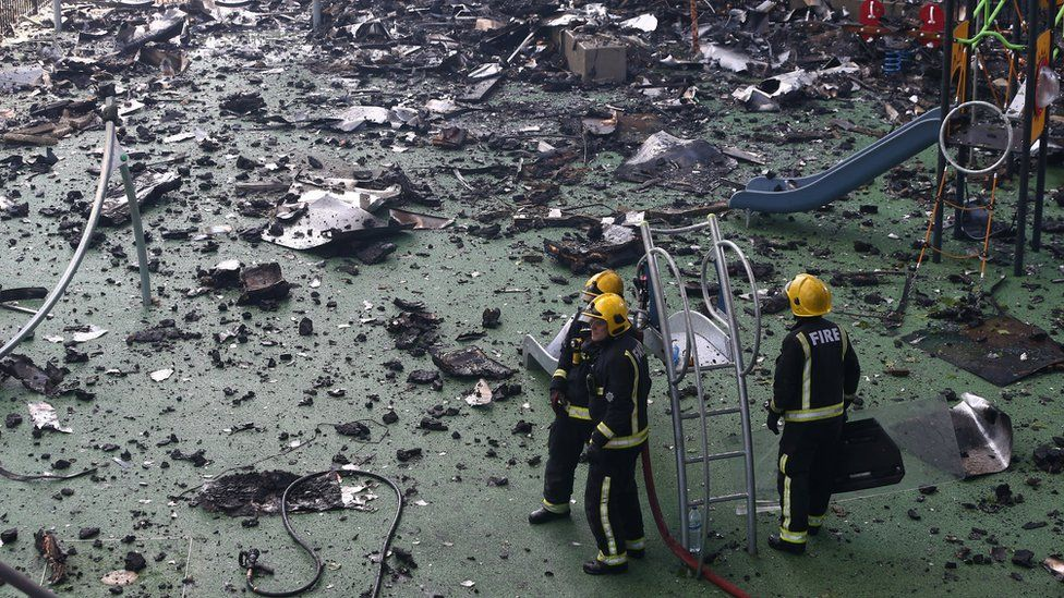 Firefighters stand amid debris in a childrens playground