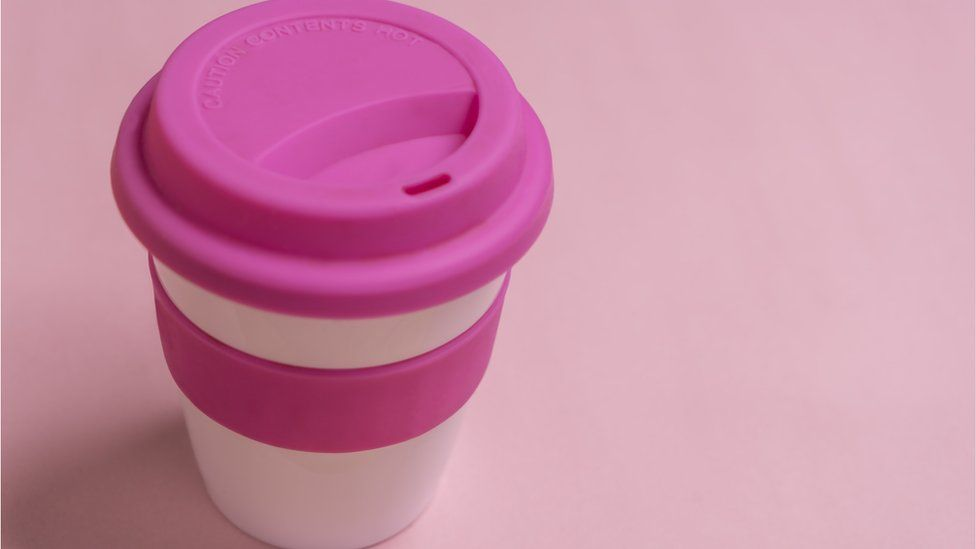 Reusable pink and white takeaway coffee mug on a pink background