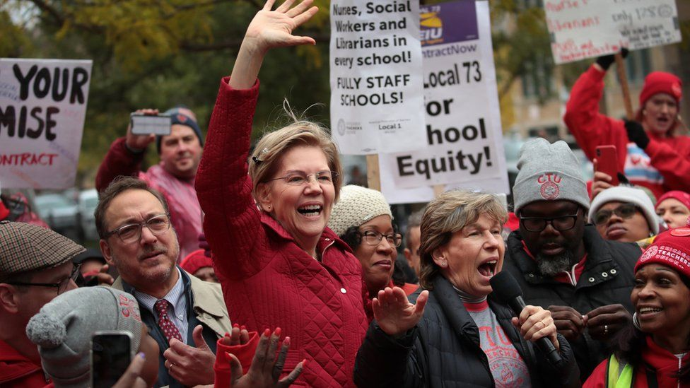 Elizabeth Warren in a crowd of teachers holding protest signs