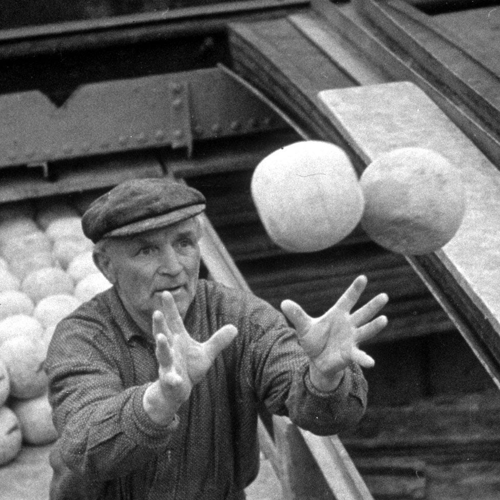 A workman catching two Edam cheeses as he loads them onto a barge for shipment to other parts of Holland (c1937)
