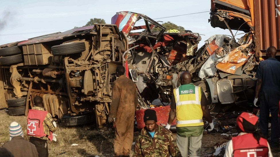 The bus wreckage is pictured on its side, heavily damaged, surrounded by emergency workers