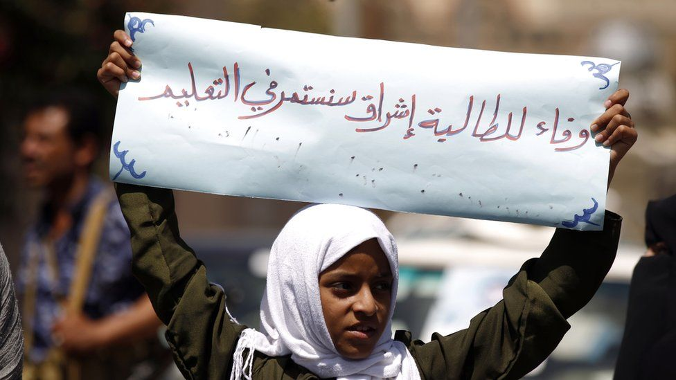 "Demonstrating outside the UN office in Sanaa, a girl holds a banner saying: ""We will continue in our education"""