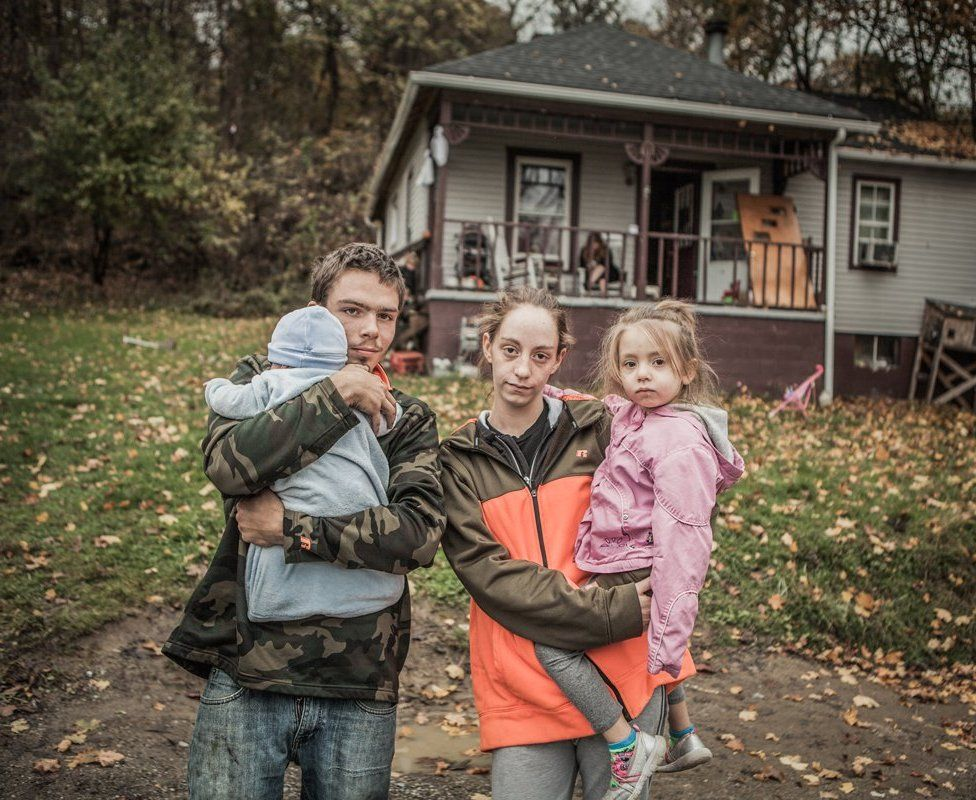 Greg and Ellen holding two children and standing outside a house