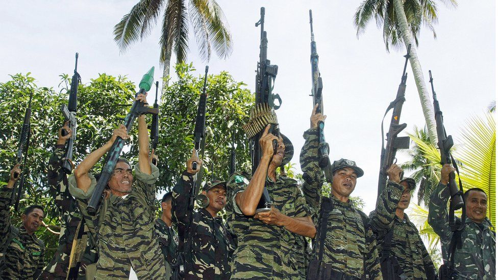 Muslim guerrillas of the Moro Islamic Liberation Front (MILF) raise their weapons during a formation in Camp Darapanan