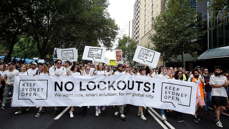 """Protesters hold a sign saying: """"Keep Sydney open. No lockouts! We want safe, smart solutions for our global city""""."""
