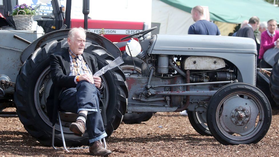 A man sits beside a vintage tractor at Balmoral Show