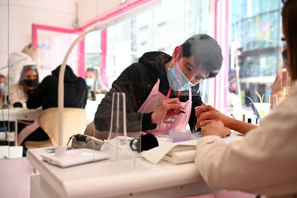 Customers sit in front of a protective screen as they have a manicure