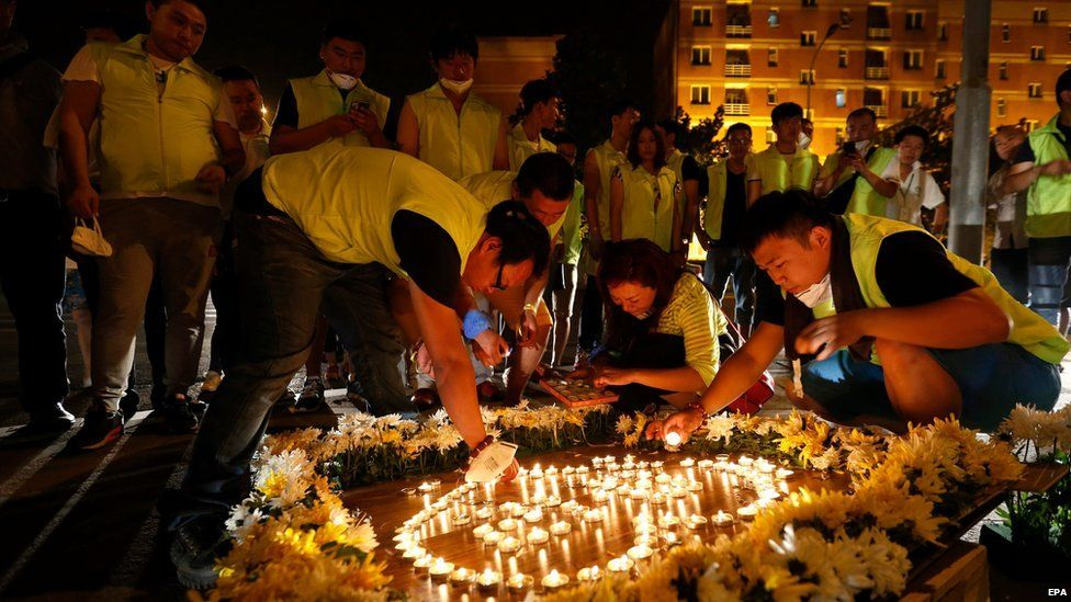 Local people pray for victims outside the Taida hospital