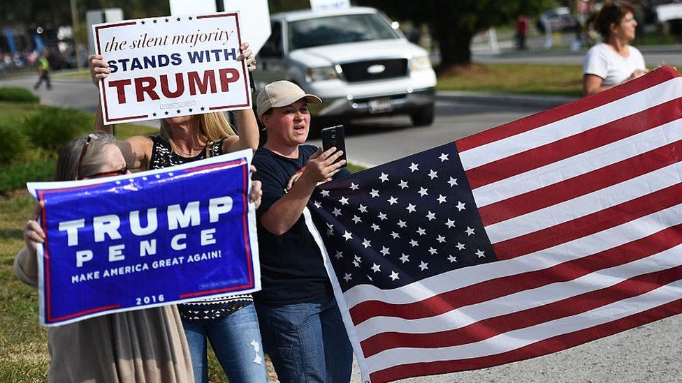 """Trump supporters hold a US flag and a sign saying """"the silent majority stands with Trump"""""""