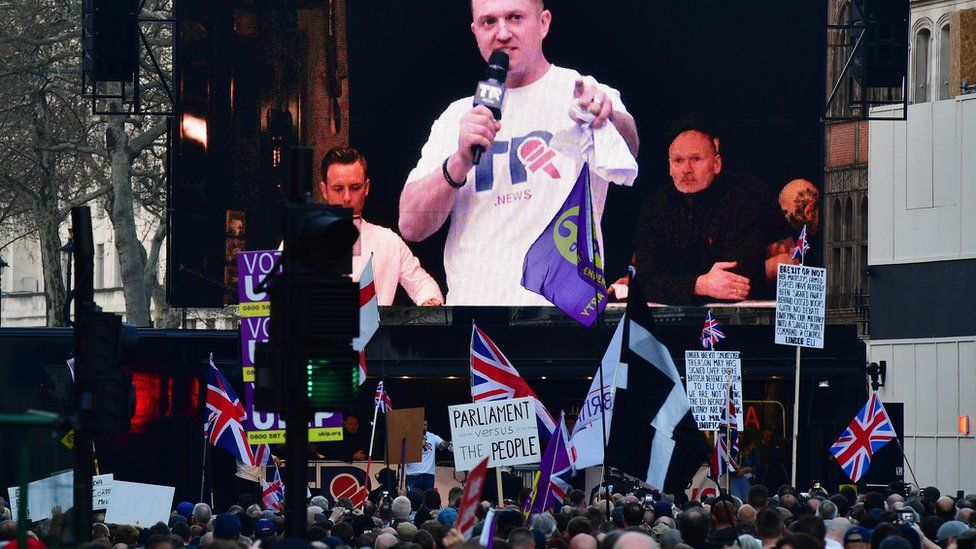 Far-right activist Tommy Robinson seem on a screen addressing protesters gathered outside the Houses of Parliament