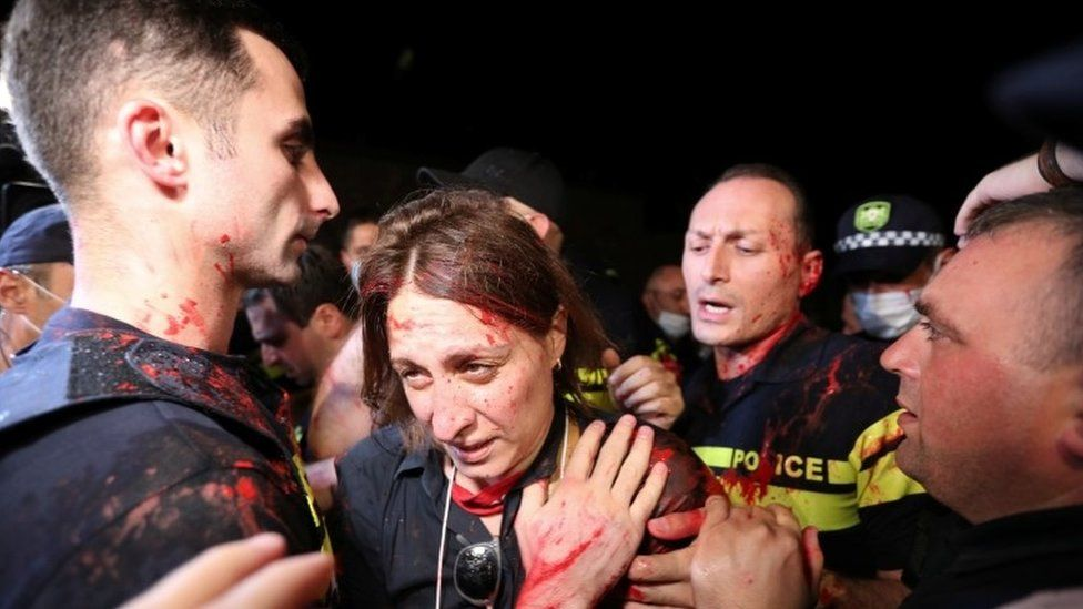 Opposition activists scuffle with police during a rally, following the death of a cameraman who was beaten up during violence against LGBT activists last week