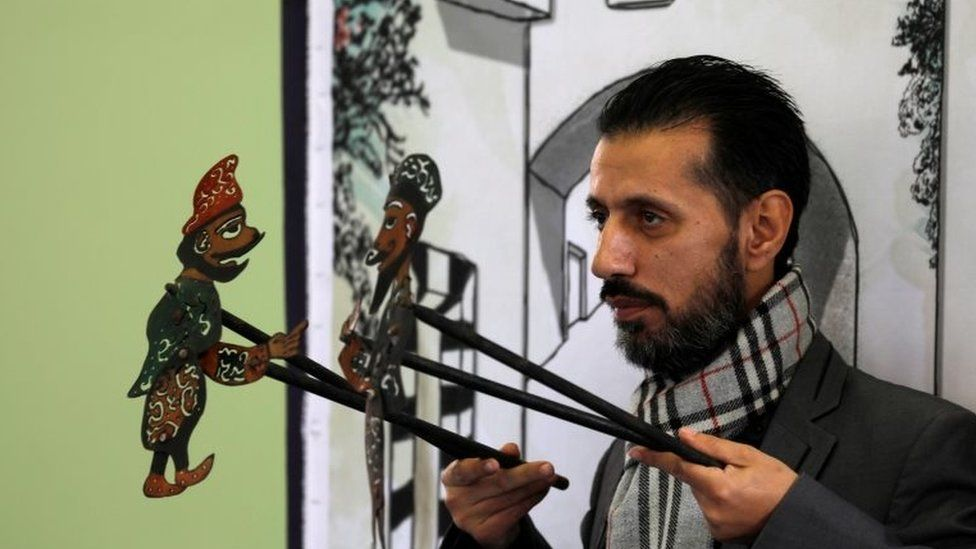 Shadi al-Hallaq, a puppeteer, holds two puppets during a performance in Damascus, Syria on 3 December 2018.