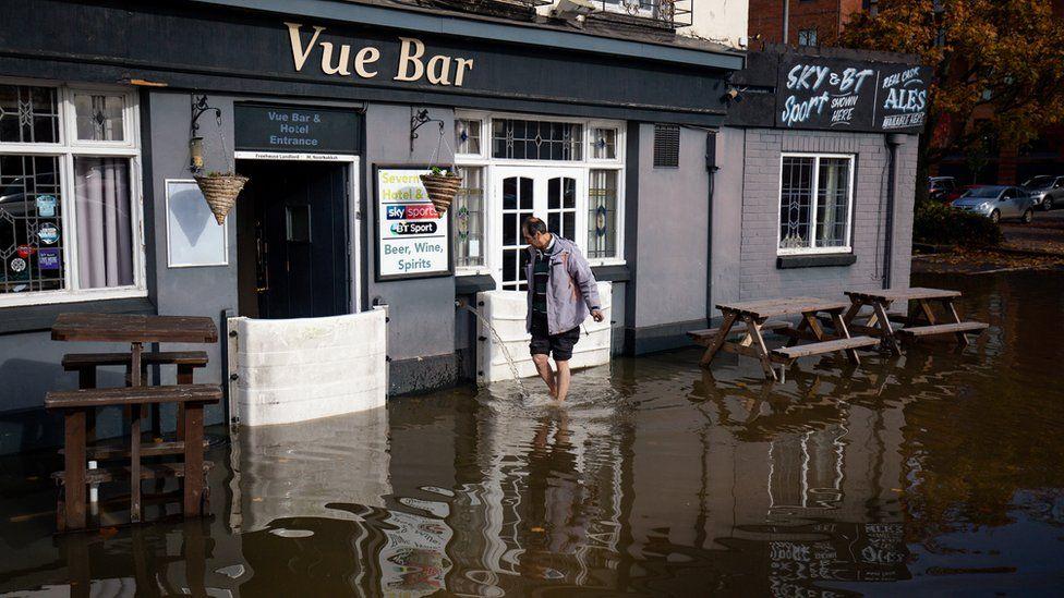 A staff member at the Vue Bar in Worcester installs flood defences