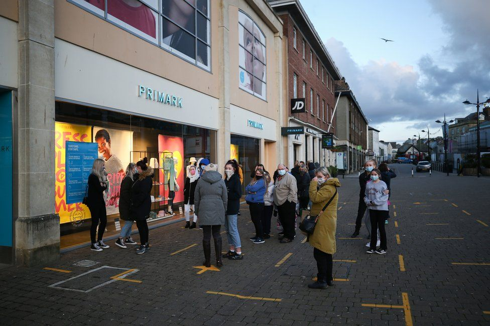 Customers queue outside of a Primark