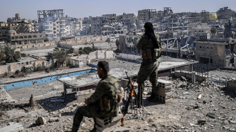 Fighters of the Syrian Democratic Forces stand guard on a rooftop in Raqqa after retaking the city from Islamic State