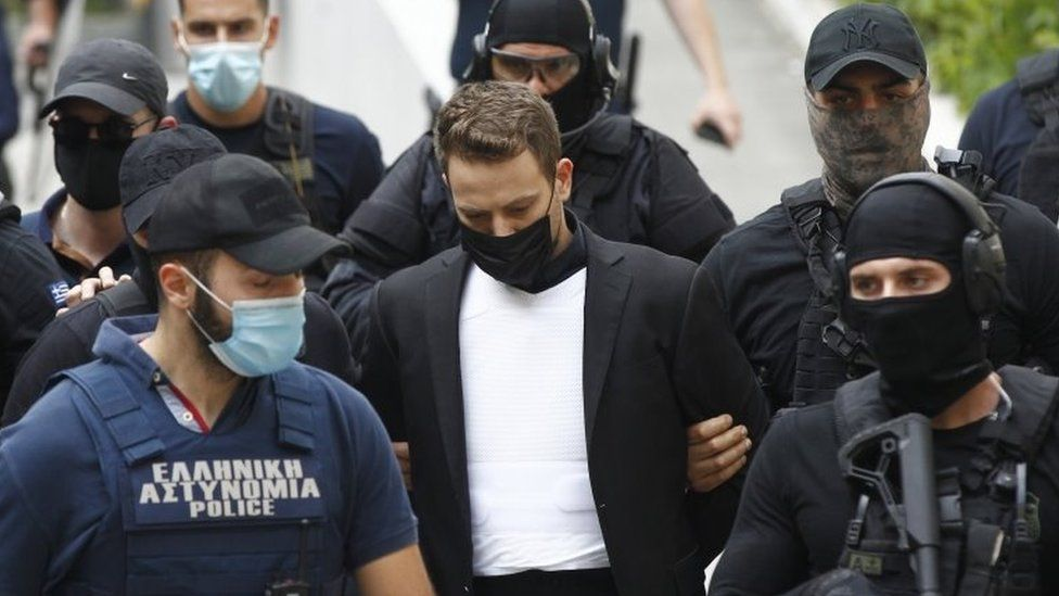 Babis Anagnostopoulos (centre) is escorted by armed police from Athens' court, Greece. Photo: 18 June 2021
