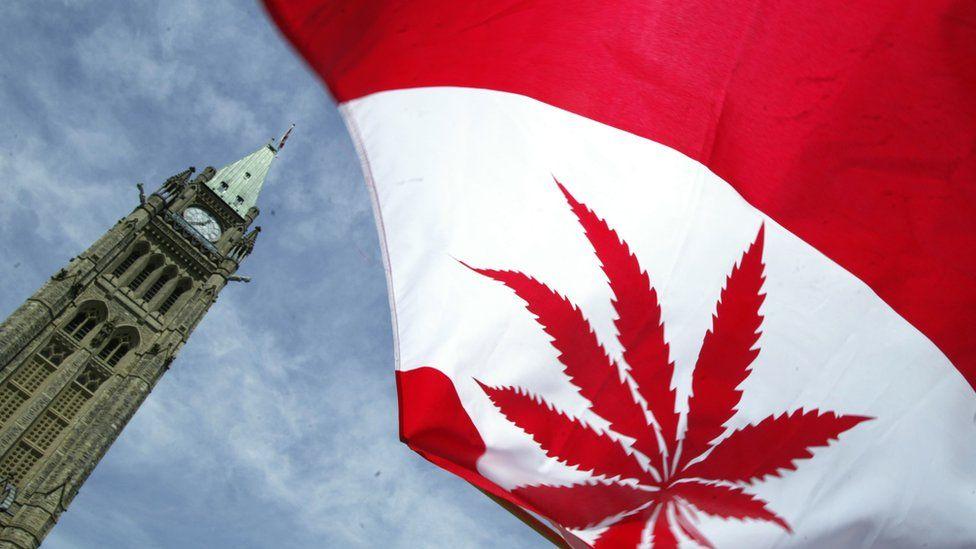 A Canadian flag with a marijuana leaf flies during a rally alongside Parliament Hill in Ottawa, Canada.