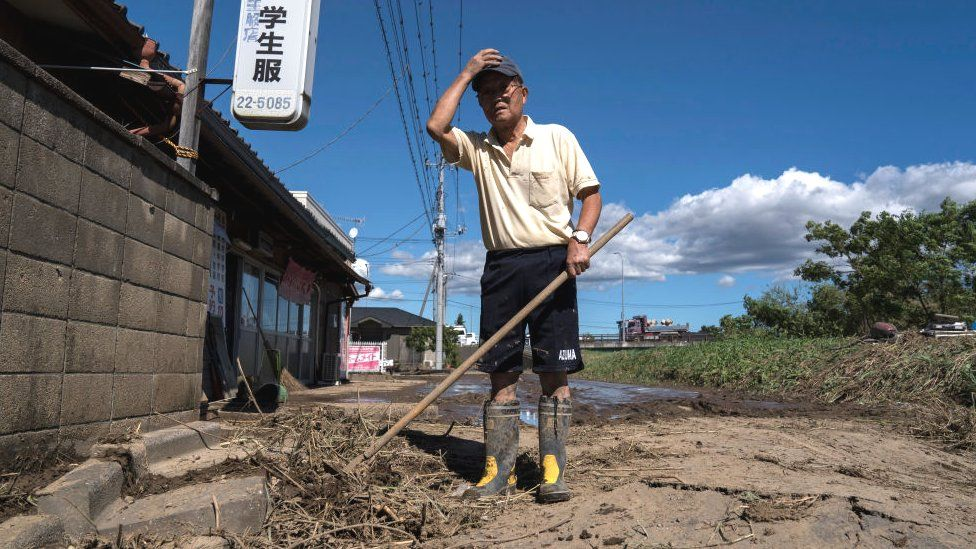 A man clears mud from his store following the passage of Typhoon Hagibis