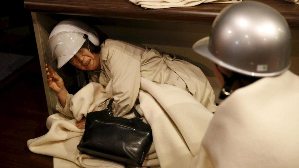 A woman takes shelter after another earthquake hit the area at a hotel in Kumamoto, southern Japan, 16 April 2016.