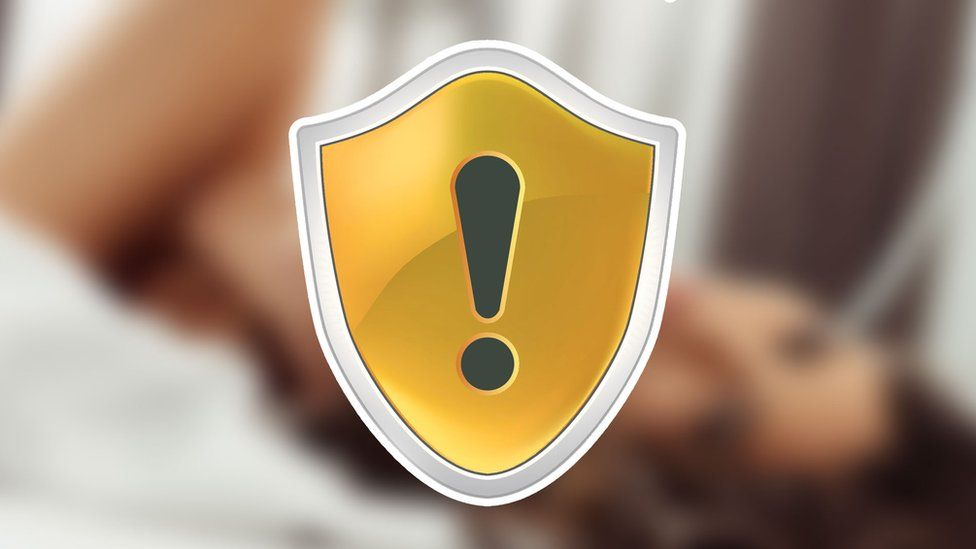 A blurred image hinting at some possibly sexual content is superimposed with a yellow warning shield