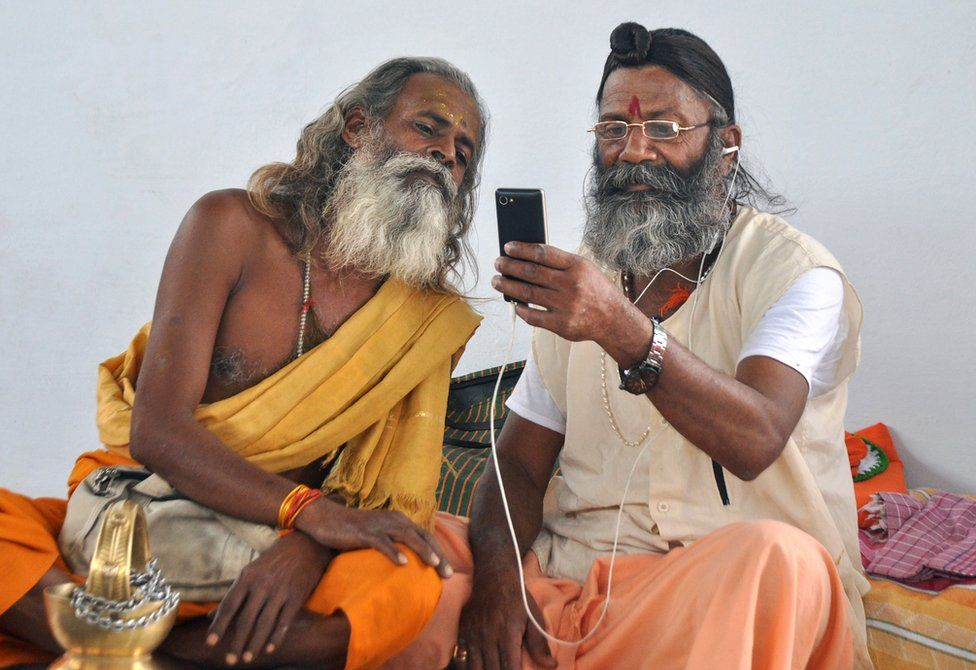Hindu holy men look at a mobile phone as at a temple