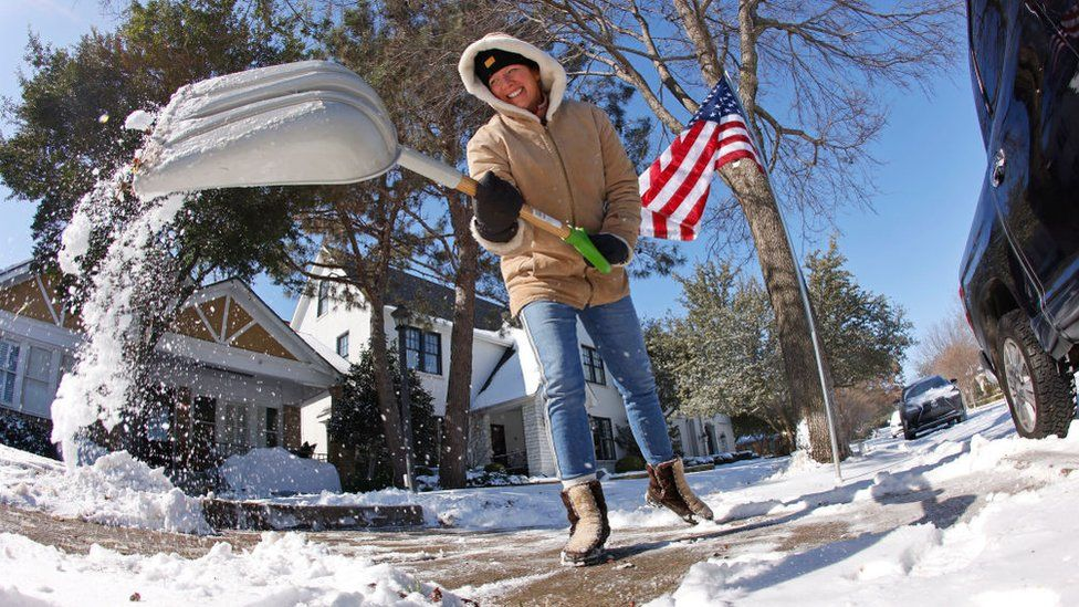 A resident shovels snow from outside her home after a storm February 15, 2021 in Fort Worth, Texas