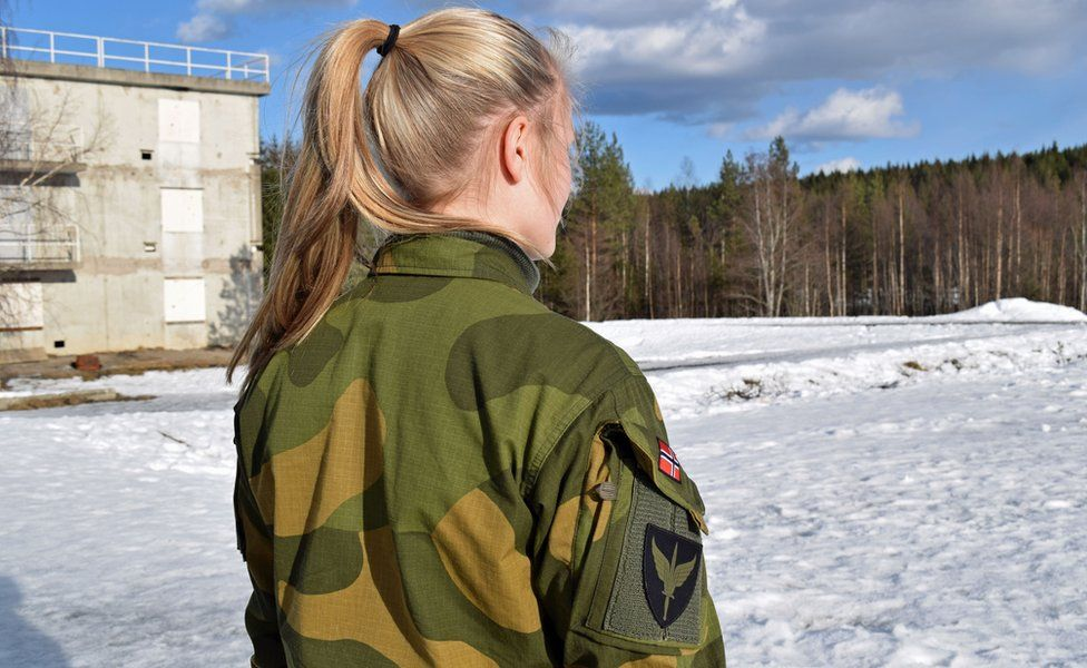 Venderla, 22, is seen from behind. She has a blonde ponytail and wears military fatigues
