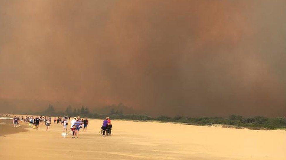 The Tathra blaze seen along the coastline as residents evacuate along the beach