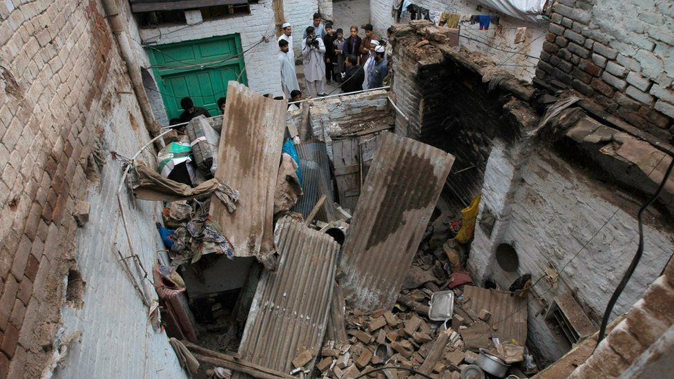 People stand outside a house damaged by an earthquake in Peshawar, Pakistan (26 Oct. 2015)