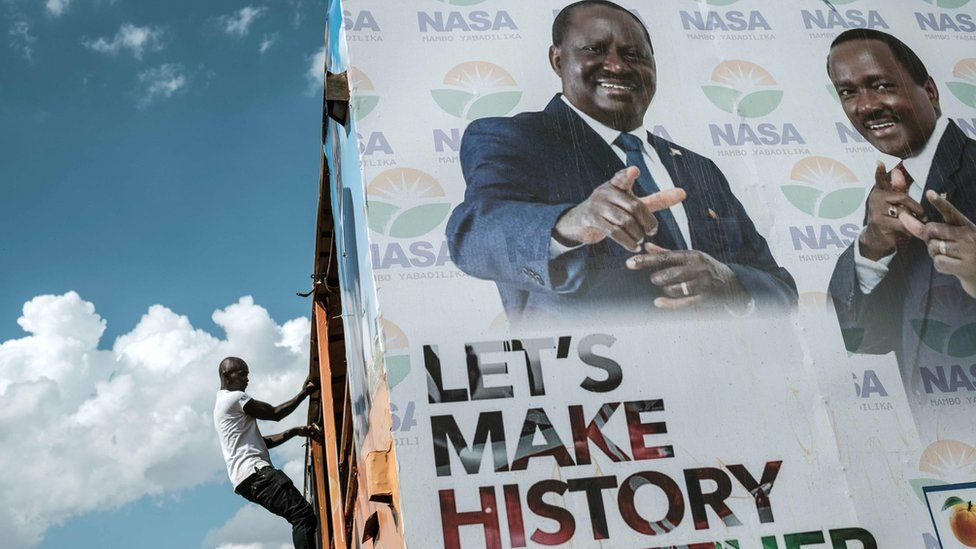 """A man climbs the scaffolding of a National Super Alliance electoral poster, set against a bright blue sky. The poster, featuring Raila Odinga, reads: """"Let's make history together"""""""
