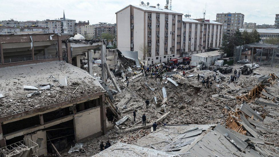 Emergency workers stand at the site of an explosion at the police headquarters in Diyarbakir, south-eastern Turkey, on 11 April 2017