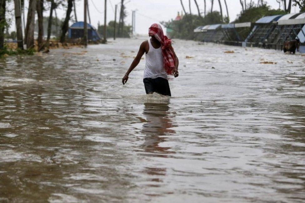 A man wades through a water-logged road after rains ahead of Cyclone Yaas at Digha in Purba Medinipur district in the eastern state of West Bengal, India, May 26, 2021