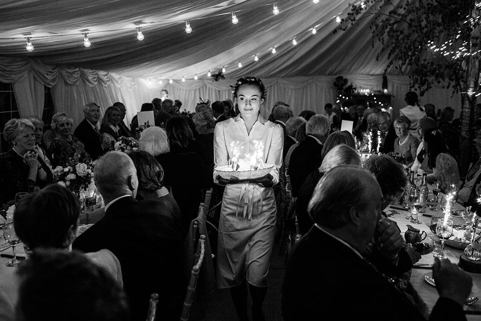 A waitress carries food through a wedding reception