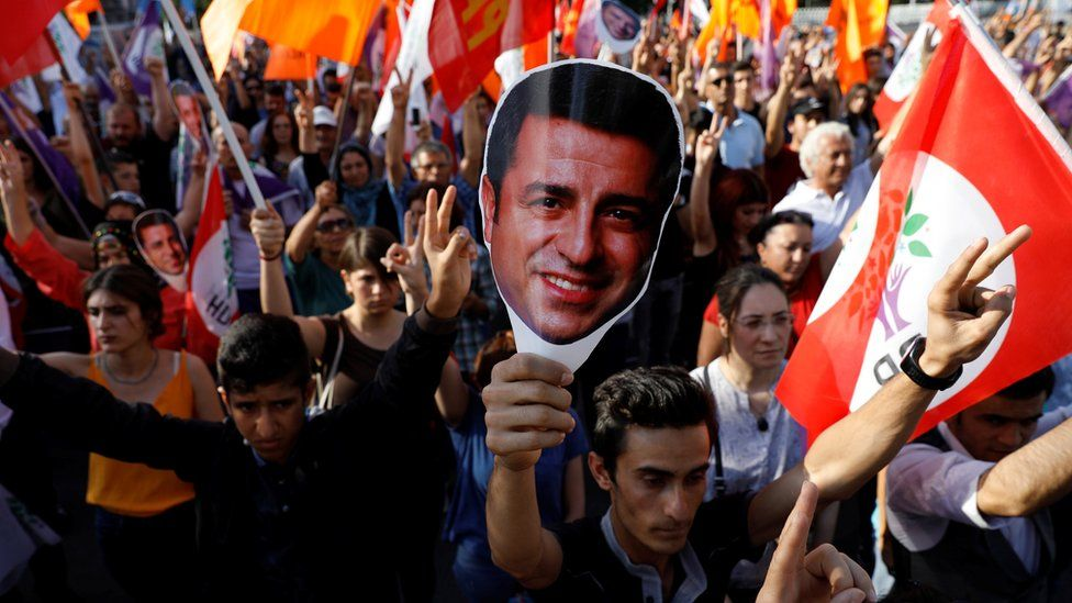 Supporters of Turkey's main pro-Kurdish Peoples' Democratic Party (HDP) hold masks of their jailed former leader and presidential candidate Selahattin Demirtas