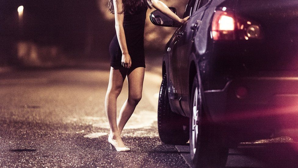 A woman standing by a car