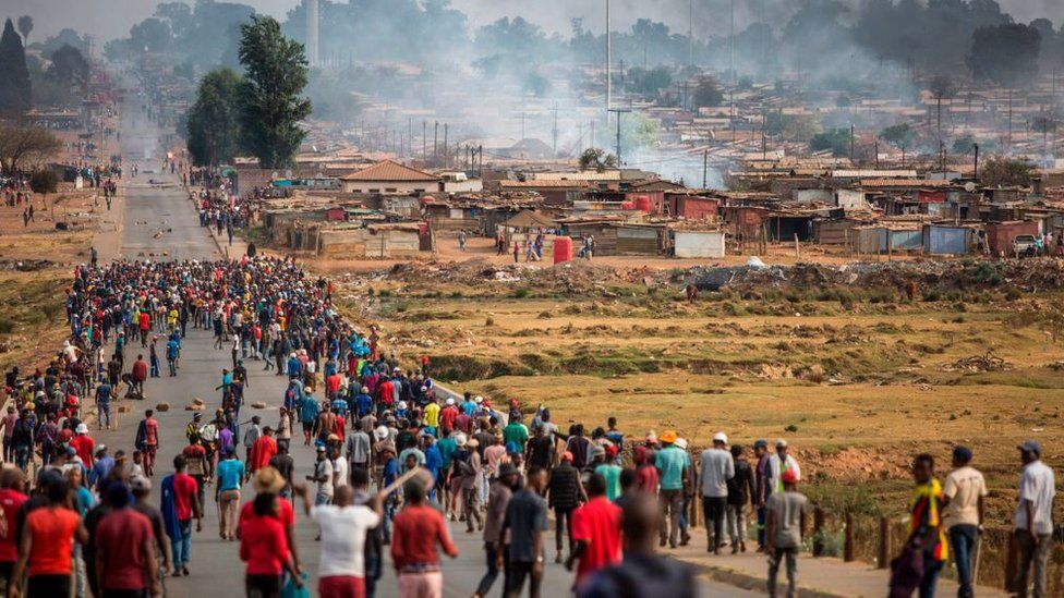 A mob armed with spears, batons and axes run through Johannesburg's Katlehong Township during a new wave of anti-foreigner violence on September 5, 2019