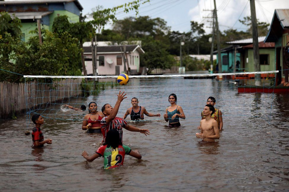 Residents play volleyball in a street flooded by the rising Solimoes river