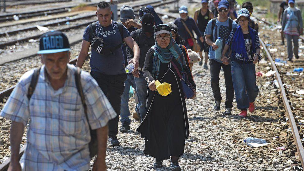 Migrants walk down a railway line in Macedonia