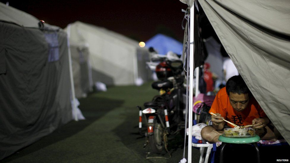 A man eats in a tent set up at a temporary shelter in a playground of a primary school, for people affected by explosions in Tianjin, China, on August 14, 2015
