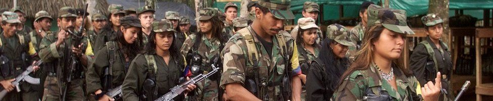 Marxist FARC rebels march through a guerrilla camp deep in the jungles of southern Colombia, 22 June 2001.